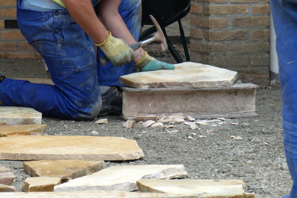 Flagstones op maat maken met een hamer.