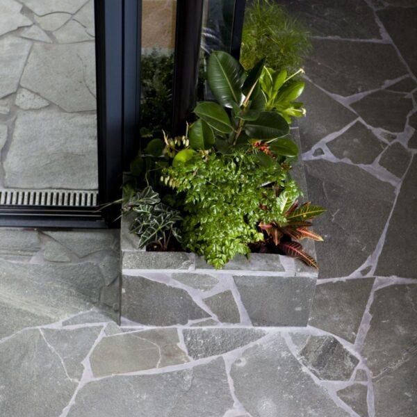 Om zoveel mogelijk in hetzelfde product te blijven, is er voor gekozen om ook de bloembakken te voorzien van Flagstones Alta Kwartsiet. Afgevoegd met ARDEX GK grijs.