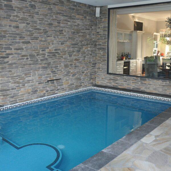 Flagstone vloer binnenzwembad en steenstrip wandbekleding