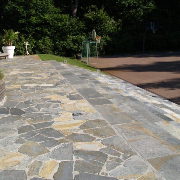 Flagstone-tegels op het terras. Voor de trap is dit materiaal gezaagd toegepast.