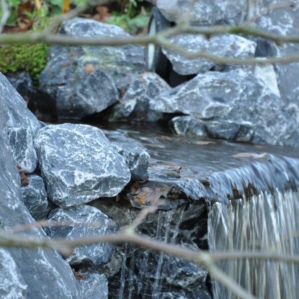 Deze Natuursteenplaat van Flagstones zorgt voor een natuurlijke waterval in de vijver.